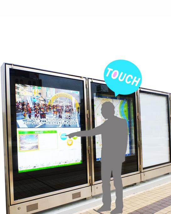 タッチセンサーを使用したデジタルサイネージをタッチしている男性の画像