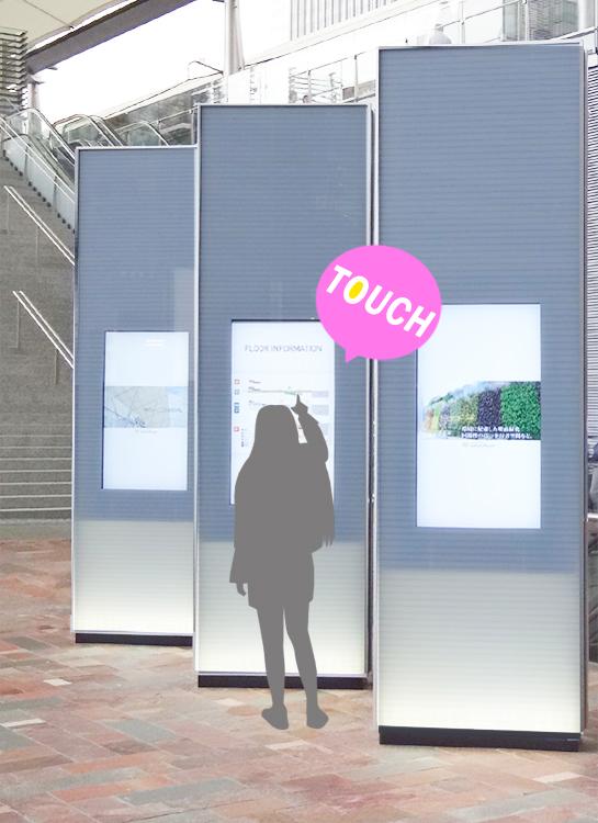 タッチセンサーを使用したデジタルサイネージをタッチしている女性の画像